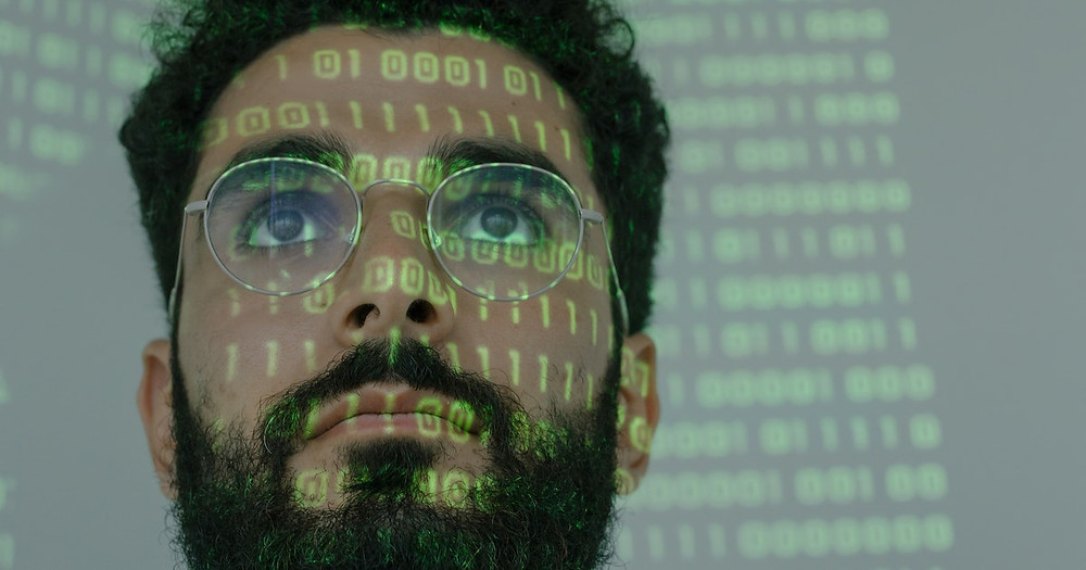 man in glasses looking at code