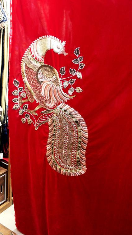Peacock on red velvet curtains