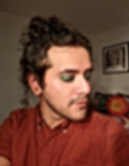 Picture of a Latinx queer poet in green glittery eyeshadow, long hair in a bun, slightly smiling with eyes closed.