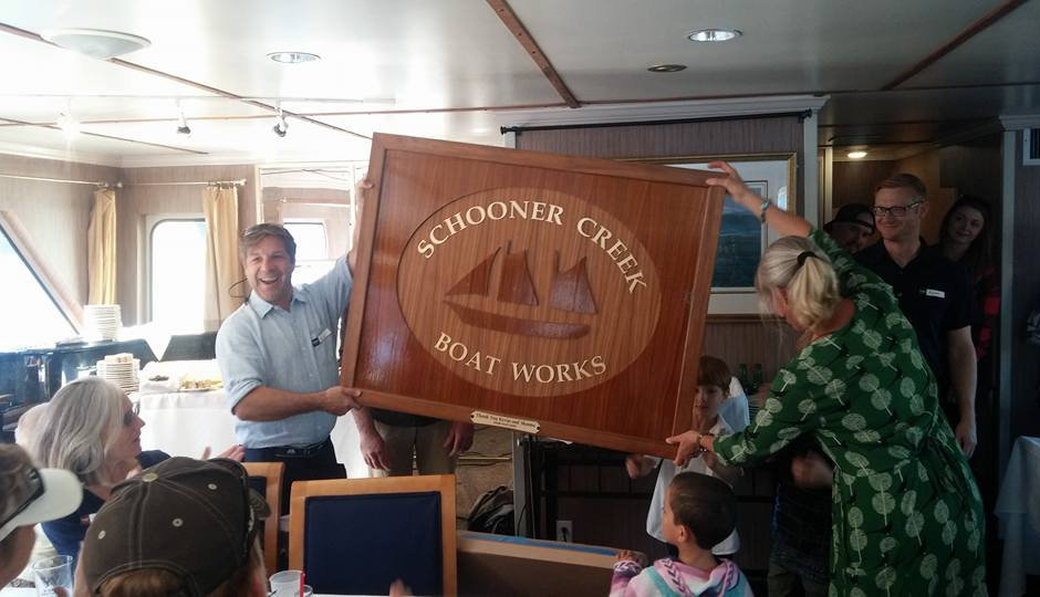 Owners Kevin and Shauna Flanigan holdin up anniversary plaque