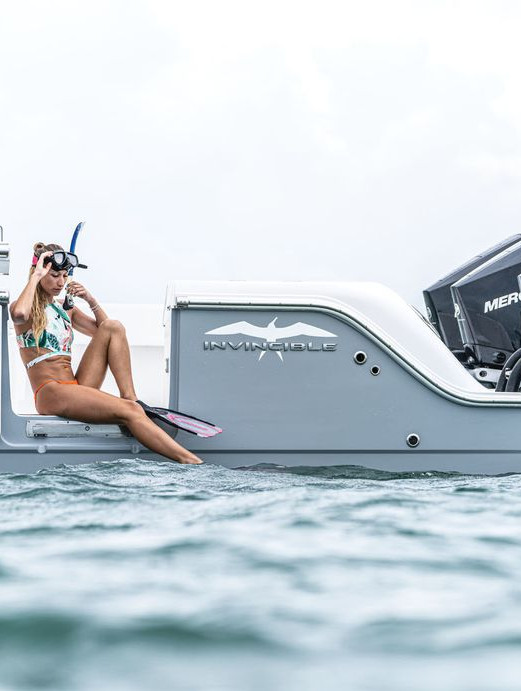 Grey Invincible Catamaran with woman fishing