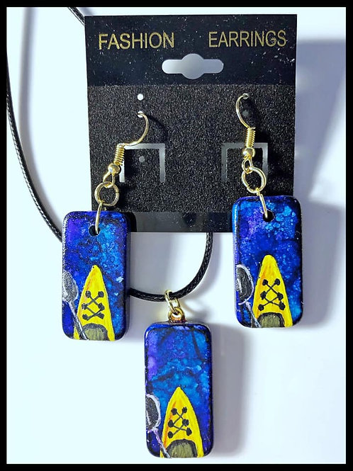 Altered domino pendant and earring set.  Blueish alcohol ink background with handpainted yellow kayak painted on the front.