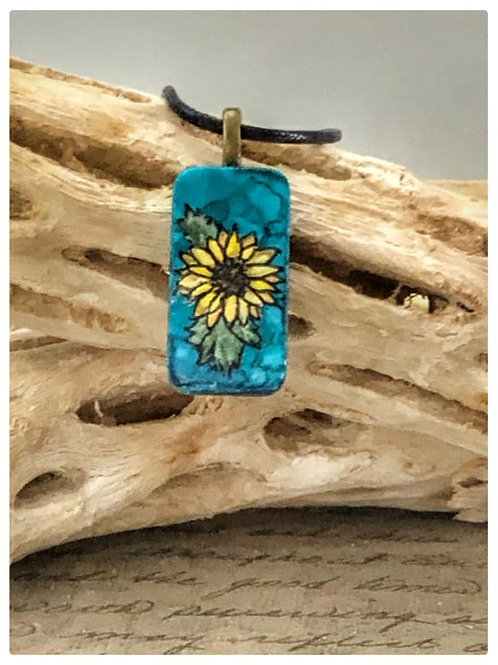 Altered domino pendant.  Blue, Teal alcohol ink background with handpainted yellow sunflower painted on the front.