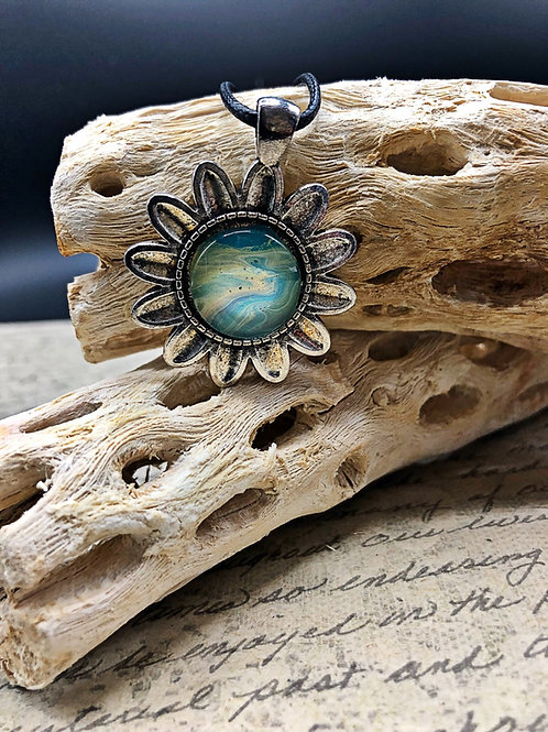 Silver flower pendant with blue and yellow acrylic painted center.