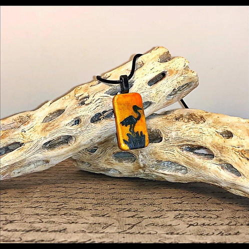 Altered domino pendant.  Orange alcohol ink background with handpainted pelican silouette painted on the front.