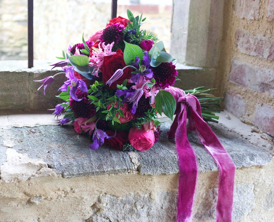 Jewel bridal bouquet of reds, purples and pinks