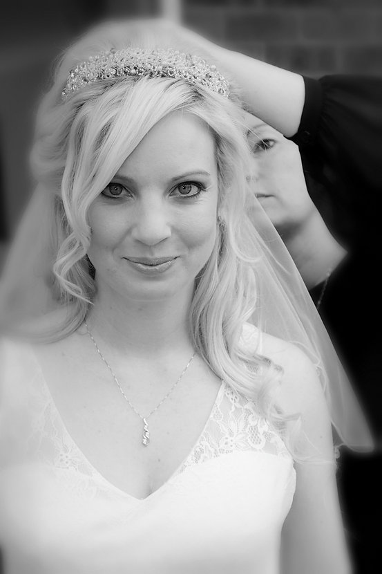 Essex wedding hairstylist adding the veil to the bride after styling her hair