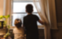 two young children look out window with their backs to the camera