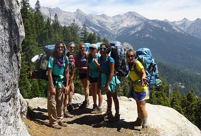 Girl Scouts Backpacking on a Cliff