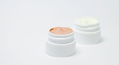 Skincare creams against a white background