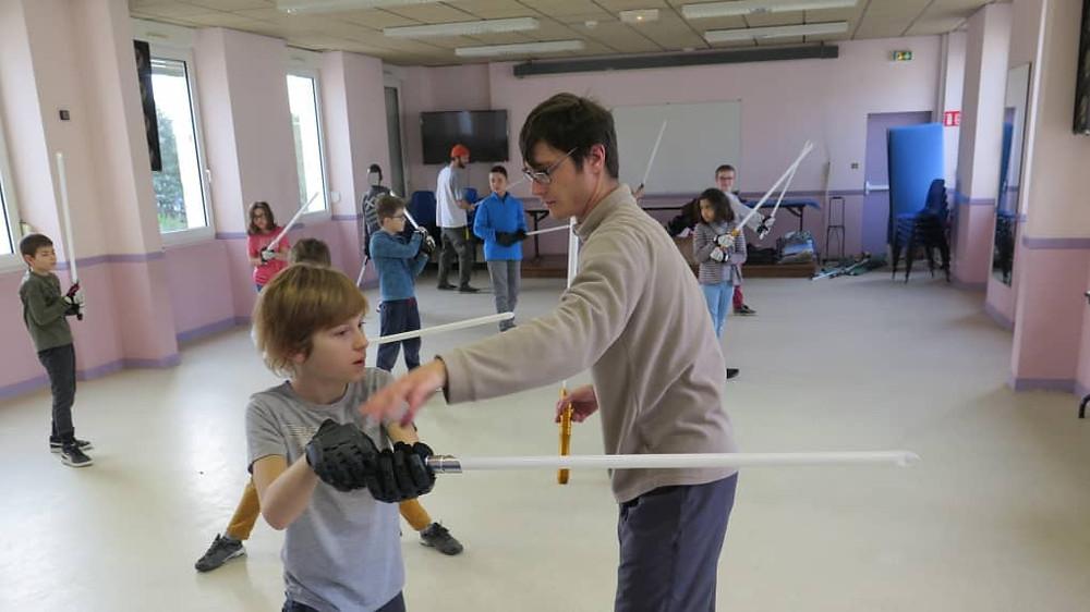 Kevin Bricout, de l'académie de sabre laser Esprit du dragon à Tours, apprend aux jeunes du centre de loisirs à manier leur arme.