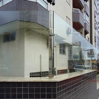 Muro de vidro e portão em aço inox