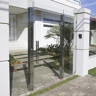Fachada com portão e muro de vidro em aço inox