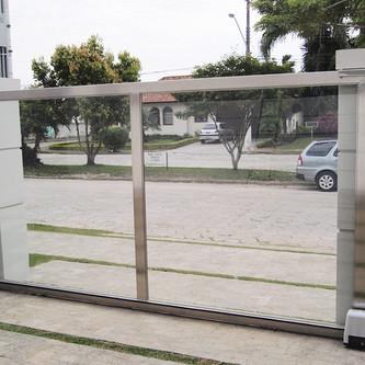 Portão de correr e muro de vidro em aço inox