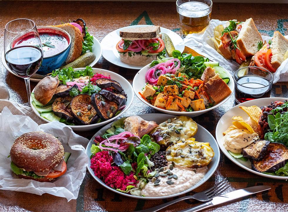 Kasvisruoka, tofua, munakoisoa ja salaattia. Uuniperunat ja bagel etualalla ja lasillinen viiniä ja keitto taustalla.