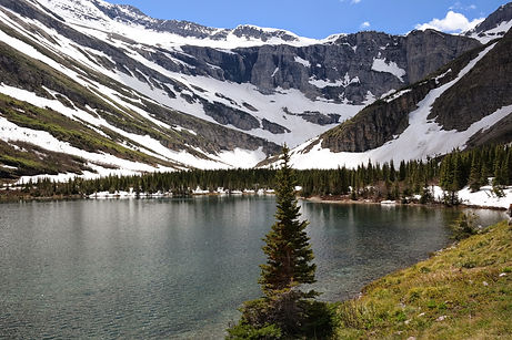 snow covered mountains behind a lake