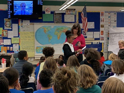 A girl skyping a classroom full of 4th graders. The teacher is holding a phone to a student asking a question
