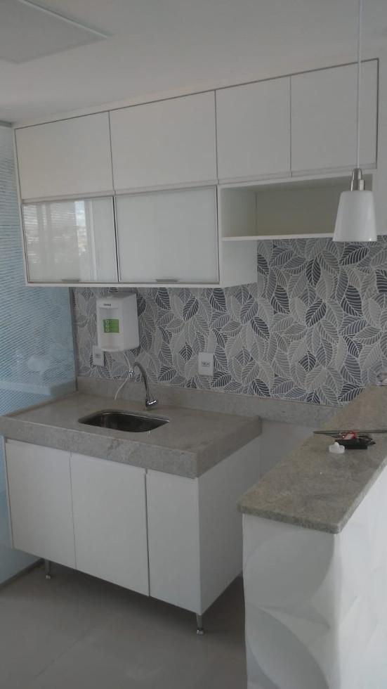 Cozinha planejada em MDF branco TX, com 2 portas de vidro laqueado branco.Puxadores cava na madeira
