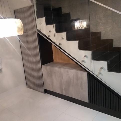 Fechamento debaixo de escada com porta e painel ripado