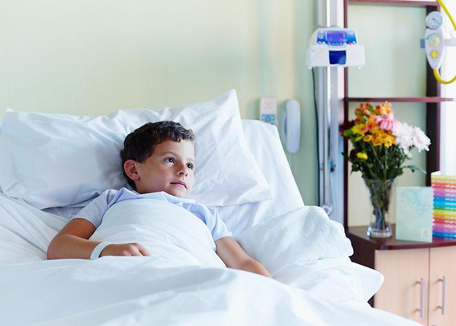 Niño en cama de hospital
