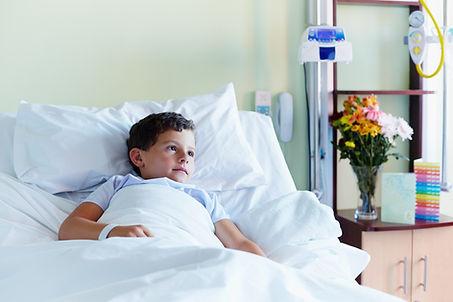 Criança na cama de hospital