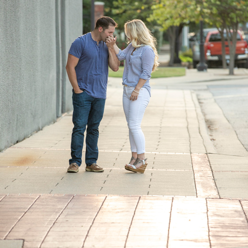young couple smiling on a sidewalk engagement photo