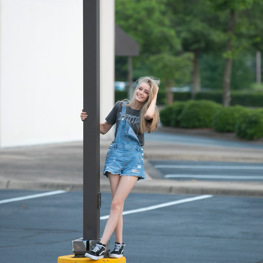Teen model in overalls posing with post