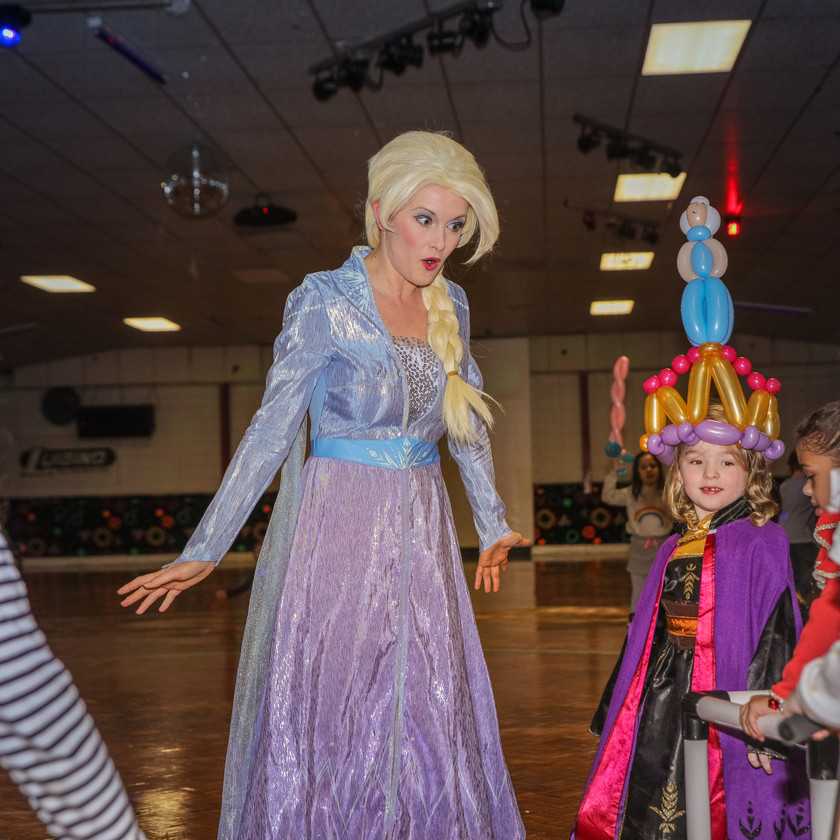 Elsa on the roller rink floor with some party attendees