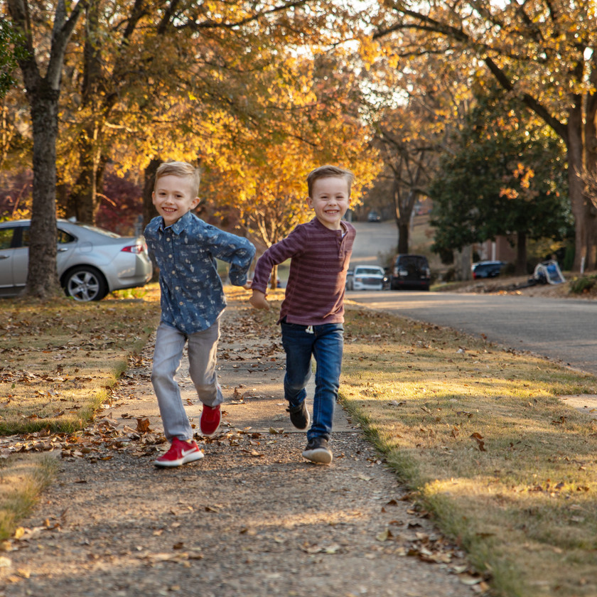 two young brothers running on autumn sidewalk in a family photo