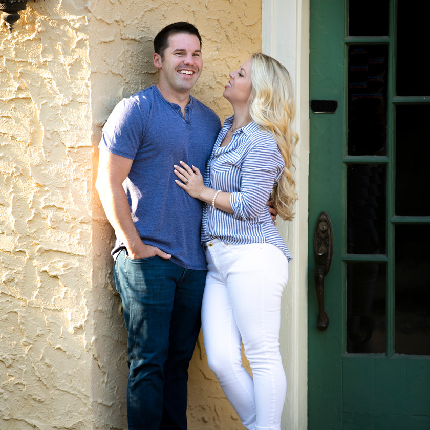 couple poses for engagement photo in front of a stone wall