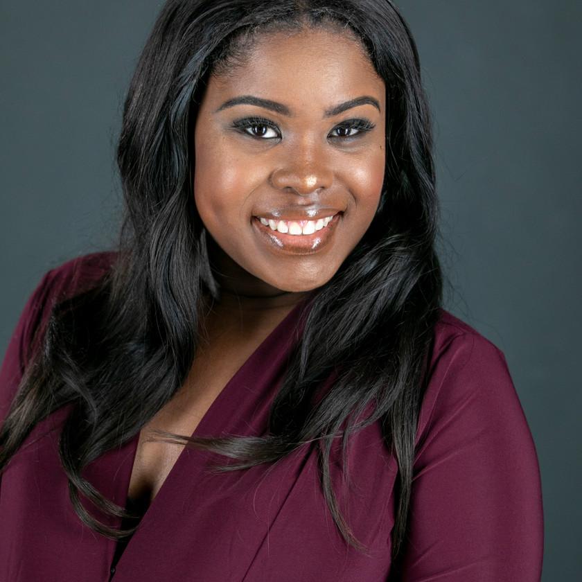 Headshot of Ebony in maroon shirt against dark gray background