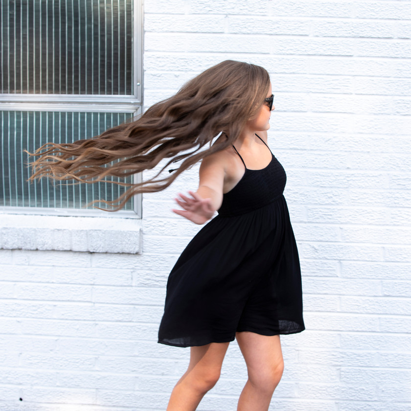 Conley posing in front of a brick wall, her hair blowing in the wind