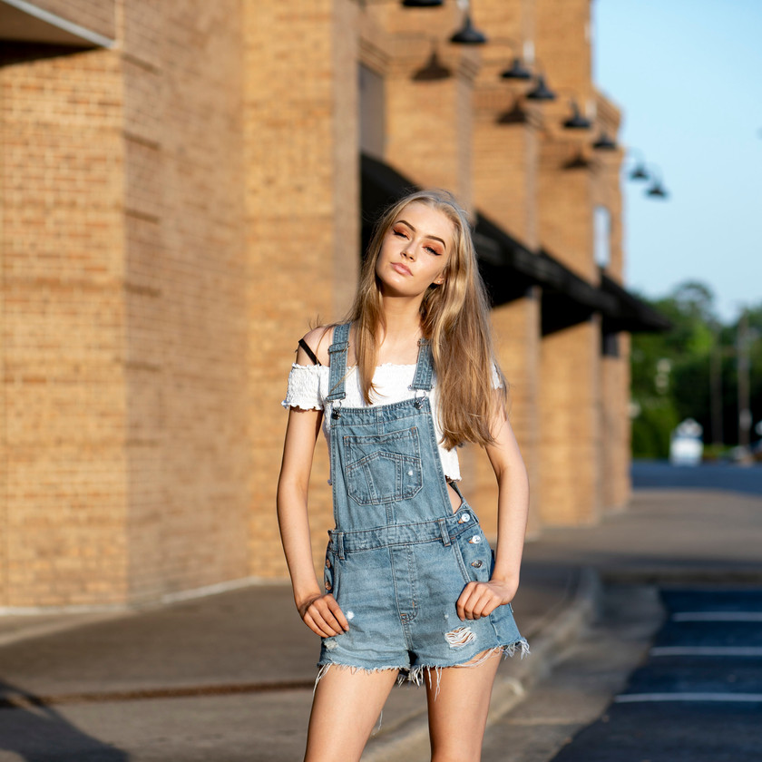 Model posing outside of brick building