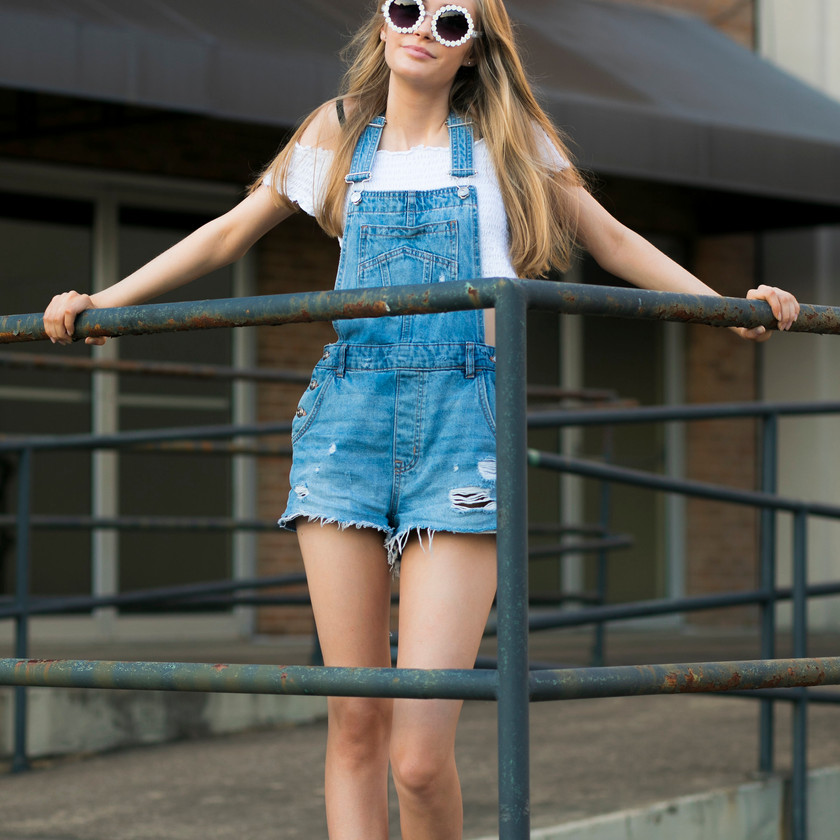 Model in front of railing wearing cutoff overalls and a white top