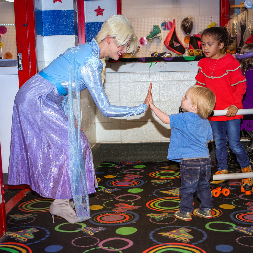 Elsa high fives a party goer at a children's birthday party