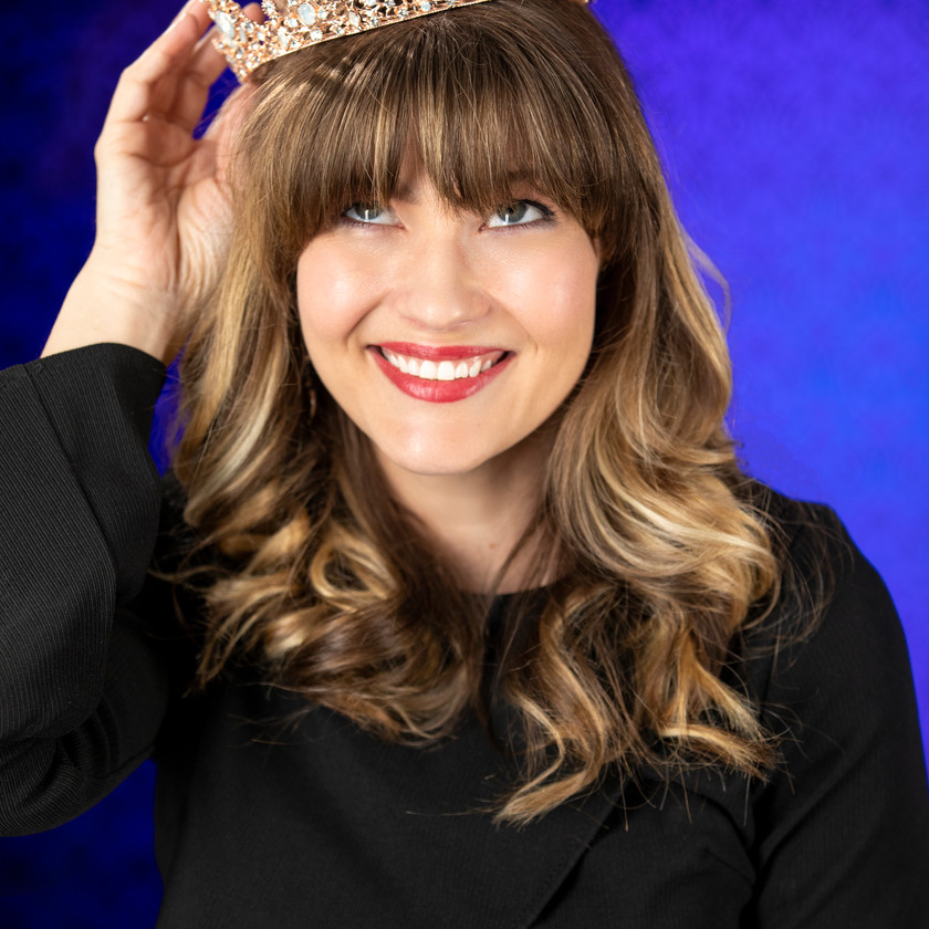 Corporate Headshot Meaghan with crown against blue background