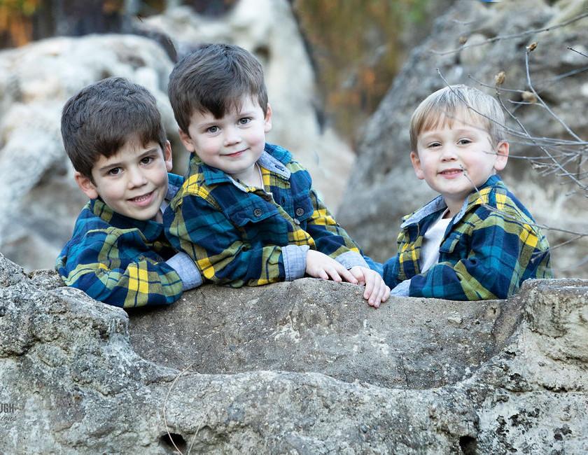 3 Young boys posing on rocks