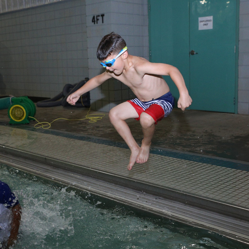 young boy jumping into the pool at a party