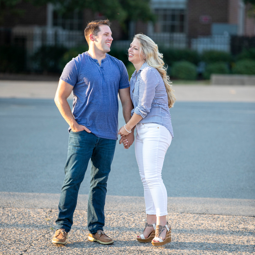 young couple holding hands in front of pond for an engagement photo