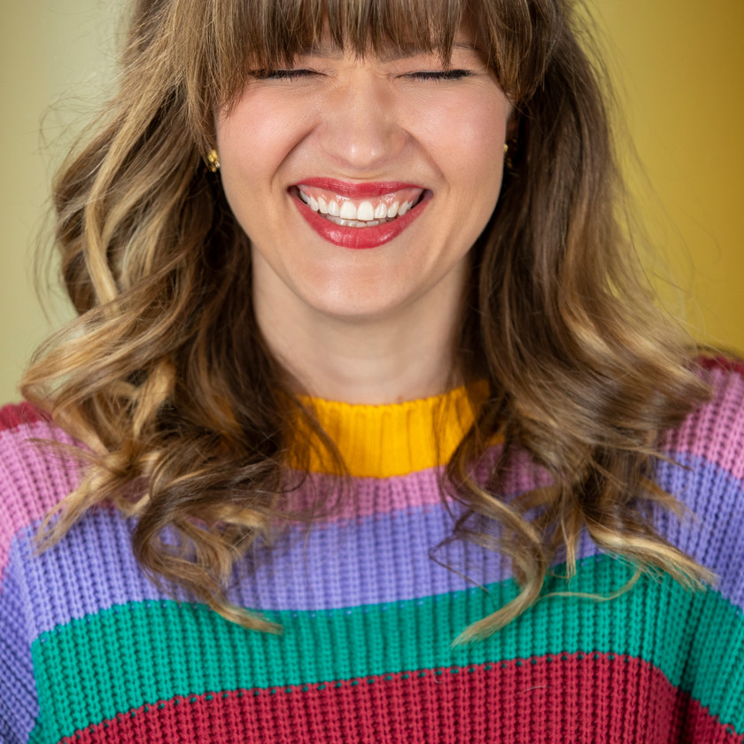 Meaghan smiling in striped top against yellow background corporate photo