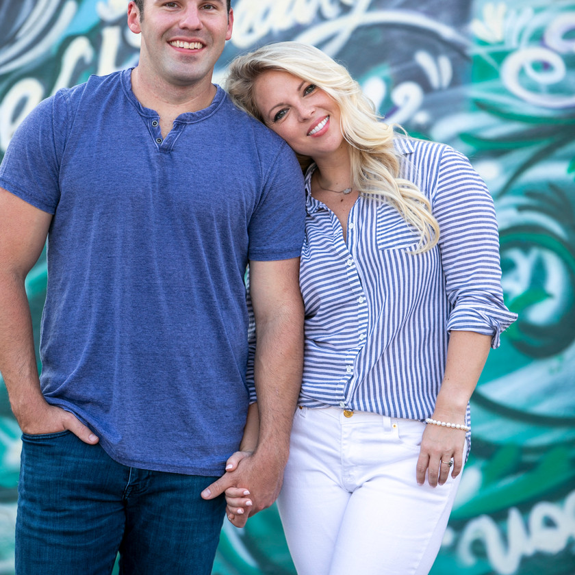 man and woman holding hands looking at the camera in a photoshoot