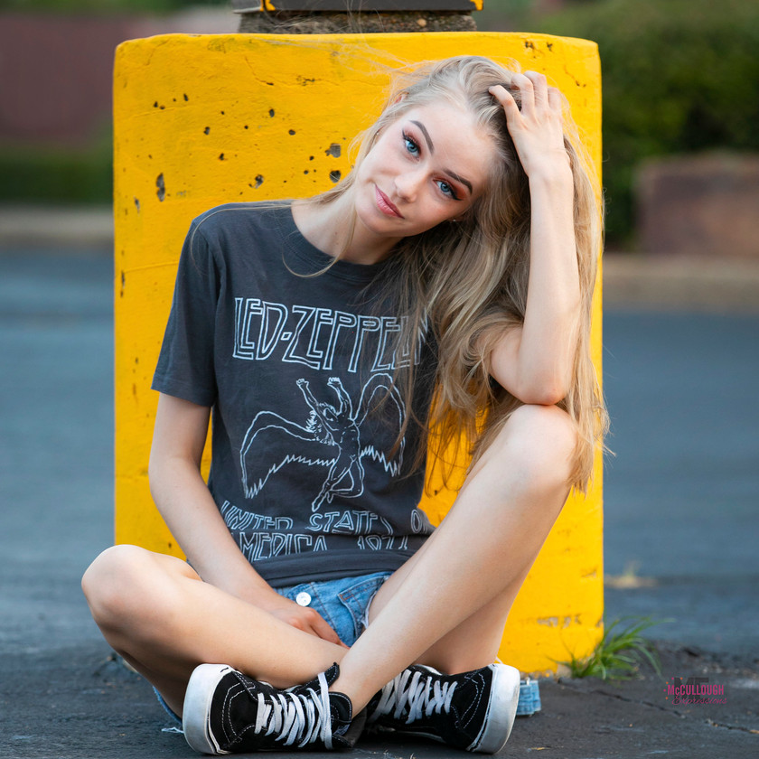 Teen model sitting in front of yellow post