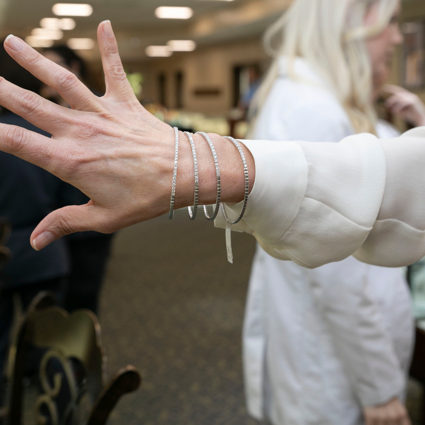 A close-up of jewelry on an event attendee's wrist