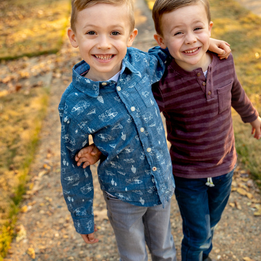 Two brothers pose for a childrens photographer on an autumn day