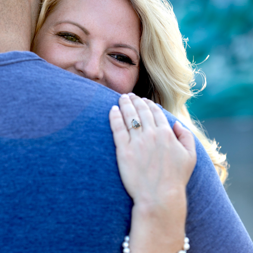 young woman hugging her fiancee in an engagement photo