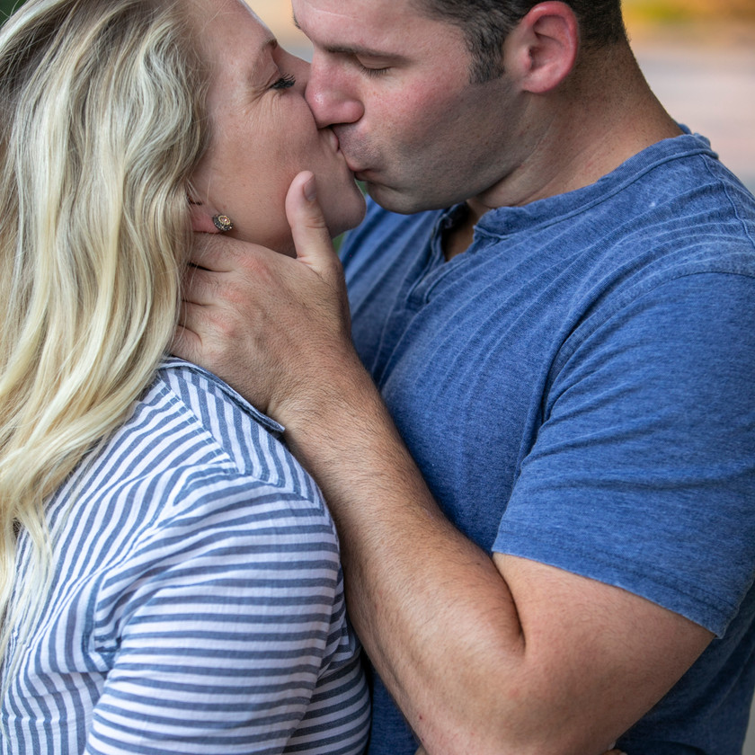 engagement photo of young couple kissing wearing blue shirts