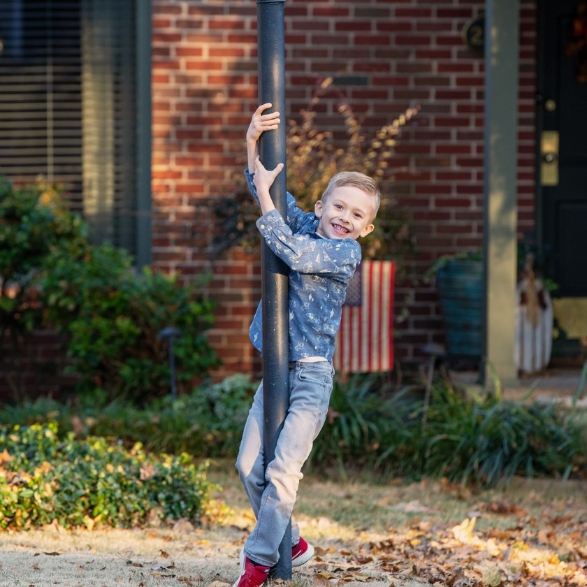 young boy poses with light post outside in autumn