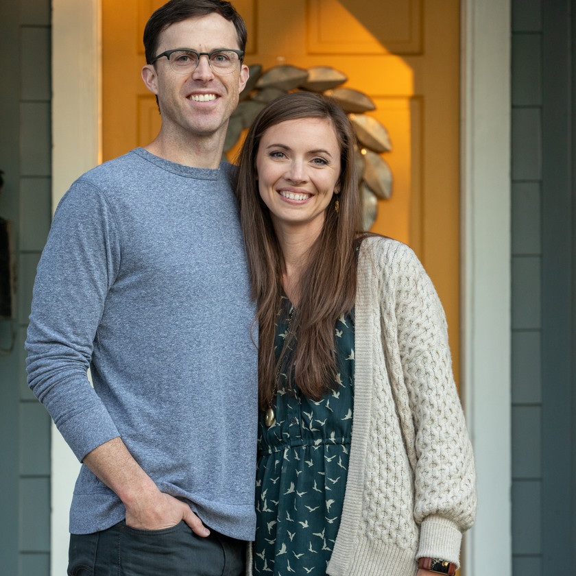 Family portrait of husband and wife in front of yellow door