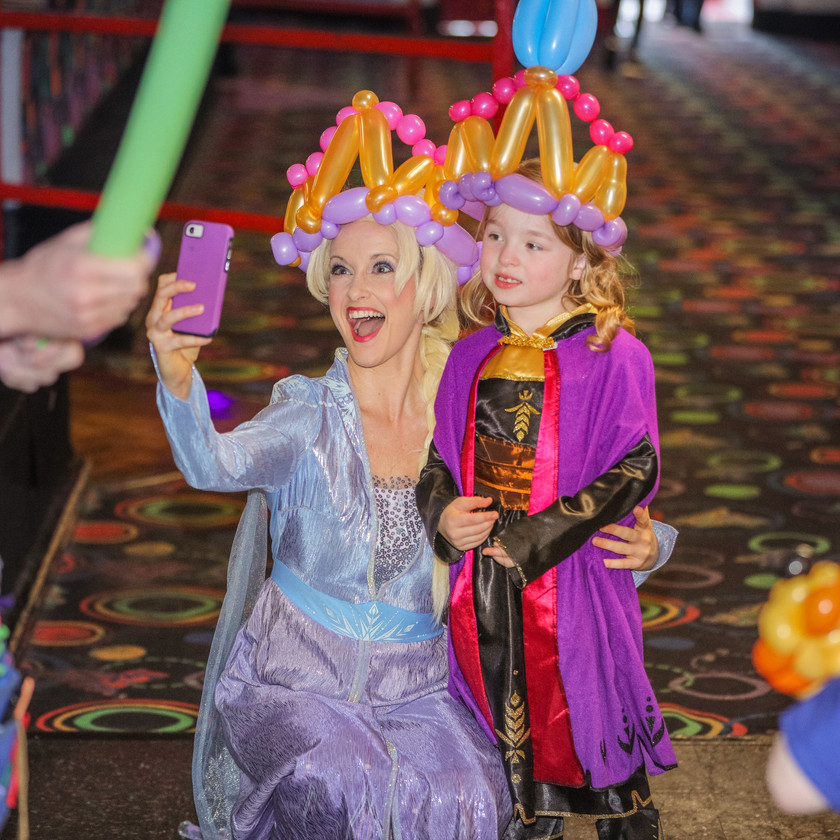 Elsa and the birthday girl pose in matching balloon hats