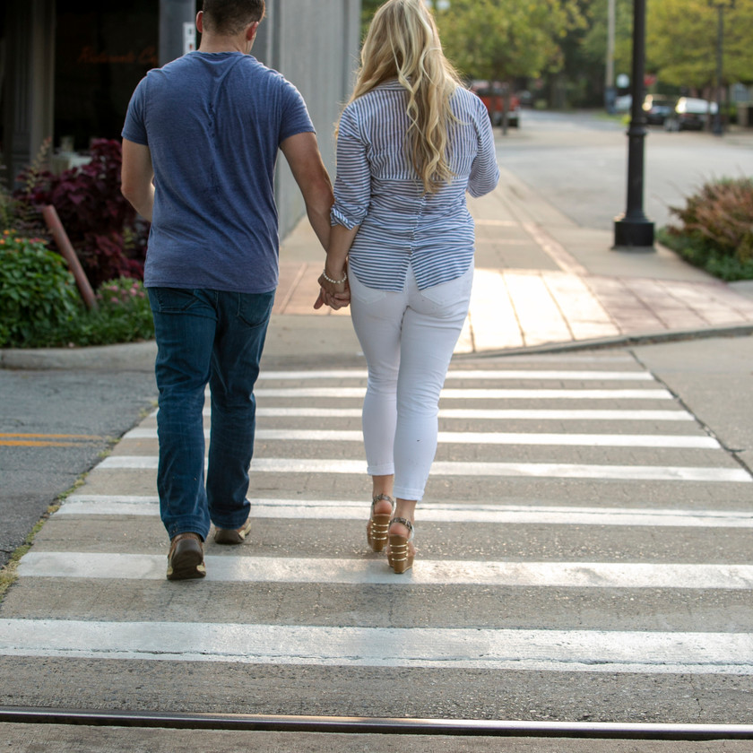 young couple walking in a crosswalk away from the photographer